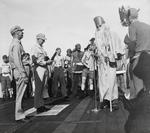 Rear Admiral Frederic Sherman, left, and Captain Carlos Wieber bid welcome to the Ruler of the Raging Main, Neptunus Rex, and his Court aboard USS Essex for the Line Crossing ceremony, 1 Sep 1944