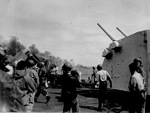 Activity continues on the flight deck of USS Essex as a crashed Japanese airplane burns off the starboard bow, 24 Oct 1944 off Luzon in the Philippines. Note Number 1 5-inch/38 caliber gun mount at right.