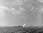 A Japanese D4Y Suisei fighter splashing into the sea after being shot down during an attack on the American fleet as seen from USS Essex, 25 Nov 1944. Note battleship USS South Dakota and US fighter in level flight