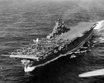 USS Intrepid under way 26 Jan 1944 on her way to launch strikes against Truk Atoll (now Chuuk). Note the forward flight deck filled SBD Dauntless and TBF Avenger aircraft and one F4U Corsair on the outrigger sponson.