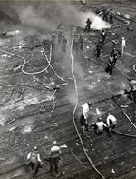 Damage control parties trying to bring fires under control on the flight deck of USS Intrepid following the crash of a Japanese special attack aircraft off the Philippines, 25 Nov 1944