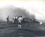 Damage control parties trying to bring fires under control on the flight deck of USS Intrepid following the crash of a Japanese special attack aircraft off the Philippines, 25 Nov 1944. Note the bulge in the deck
