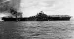 The carrier Franklin burning and listing badly after bomb hits aft set off more bombs and fueled aircraft, 19 Mar 1945. Note burning fuel pouring off the hangar deck and dislodged forward elevator.
