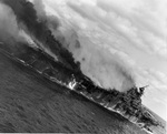 Angled view of the carrier Franklin burning and listing badly after bomb hits aft set off more bombs and fueled aircraft, 19 Mar 1945. Note burning fuel pouring off the hangar deck.