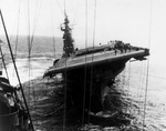 The carrier Franklin still listing badly after fires were brought under control following bomb hits aft that set off more bombs and fueled aircraft, 19 Mar 1945.