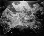 Strike photo taken by USS Hancock aircraft showing an attack on the Yokosuka Navy Yard, Tokyo Bay, Japan, 18 Jul 1945. Note bomb splashes.