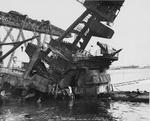 Badly damaged USS Arizona foremast structure, bridge, and top of turret number 2 in Pearl Harbor, Hawaii, 17 Feb 1942. Note floating crane YD-25 at left