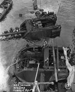 Salvage work continuing on the sunken battleship USS Arizona in Pearl Harbor, Hawaii, 25 Feb 1942. Note Arizona's two after main turrets being pumped out and disassembled.