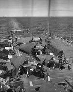 USS Belleau Wood after fires were put out and damaged aircraft were jettisoned after being struck by a special attack aircraft earlier in the day, off the Philippine Islands, 30 Oct 1944. Note hole in flight deck