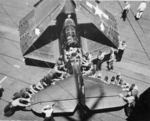 Overhead view of plane handlers spotting an SB2C Helldiver aboard USS Bennington, early 1945. This view offers a good look at the large surface area of the Helldiver's tail plane.