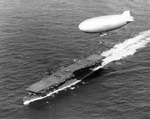 USS Langley underway off Cape Henry, Virginia, United States, 6 Oct 1943; note SNJ aircraft on flight deck and K-class airship from Lighter Than Air Squadron ZP-14 overhead.