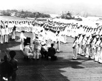 Admiral Chester Nimitz aboard USS Enterprise to present awards, Pearl Harbor, Territory of Hawaii, 27 May 1942. Note capsized USS Oklahoma and sunken USS West Virginia and USS Arizona in the background.