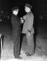 Commodore Leslie Gehres standing at attention while Vice Admiral Jack Fletcher presents him with the Legion of Merit award, Adak, Alaska, 19 Jan 1944. Photo 2 of 2.
