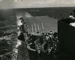 Looking aft from the signal bridge of USS Lexington (Essex-class) with 40mm Bofors mount and two 5-inch/38 mounts as F6F Hellcat approaches for a landing, Jun 1944