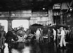 Burned and demolished F6F-5 Hellcat on the hangar deck of USS Ticonderoga following a special attack plane crashing through the flight deck and exploding in the hangar deck southeast of Formosa (Taiwan), 21 Jan 1945.