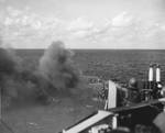 Smoke pouring through a large hole in the Ticonderoga's flight deck from fires after a special attack aircraft crashed through the deck off Formosa (Taiwan) on 21 Jan 1945