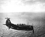 An SB2C Helldiver of Bombing Squadron VB-7 flying over USS Hancock off Formosa (Taiwan), 13 Oct 1944