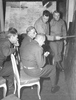 "MGen ER ""Pete"" Quaseda, with pointer, conducting an Air-Ground Liaison briefing for LtGen Carl Spaatz (glasses) and LtGen James Doolittle (seated), VII Corps Headquarters, Münsterbusch, Germany, 19 Nov 1944"