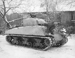 Sgt Dee Perry of the 10th Armored Division applying winter paint to his M4 Sherman tank in Belgium, 12 Jan 1945.