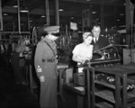 Chinese Army officer and an executive of the John Inglis and Company observing a female worker at the Inglis Toronto plant, Canada, 20 Aug 1943