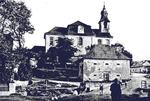 Lidice, Czechoslovakia in the 1930s. St. Martin's church built in 1732 with one of the village's barns in the foreground.