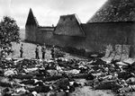 Lidice, Czechoslovakia 10 Jun 1942. SS officer standing over the bodies of all 173 of the village's men in the garden at the Horák family farm. The mattresses were put up against the stone wall to prevent ricochets.