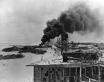 Fires and damaged buildings at Midway from Japanese bombardment during the opening of the Battle of Midway, 4 Jun 1942.