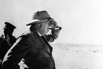 During an inspection tour to El Alamein, Egypt, Winston Churchill looks out across the desert toward the German lines, 19 Aug 1942.