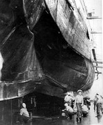 Crews inspecting midship torpedo damage to the heavy cruiser USS Chester in the Sutherland drydock at Cockatoo Island Dockyard, Sydney, Australia, Nov 1942.