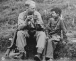 US Army Signal Corps photographer Private Arthur W. Hedgo with Chinese boy Lee Ting Yow, northern Burma, 6 May 1944
