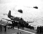 This TBF-1 Avenger attempted to land on the carrier USS Charger but missed the arresting wires and ended up tangled in the port catwalk, Chesapeake Bay, United States, 16 Mar 1943. Note US Coast Guard boats alongside.