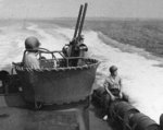 Combat training exercises aboard PT-107, an 80-foor Elco torpedo boat, circa 1942. Note twin Browning M2 .50 caliber machine guns and sailor astride Mk 6 depth charge.