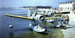 Line of OS2U Kingfisher float planes running up their engines prior to a practice flight at a training base in the United States, 1939-40.