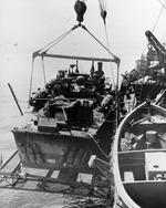 PT-325, an Elco 80-footer of Motor Torpedo Boat Squadron 21 (MTBRon 21) being hoisted aboard PT Boat tender USS Cyrene in San Pedro Bay, Leyte, Philippines, Jan 1945.