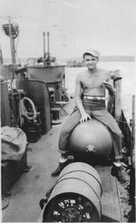 Torpedoman Second class Richard Malecki sitting astride a Mark XIII aerial torpedo aboard PT-184, May 1945. Note Mark 6 Depth Charge in the foreground and a twin Browning .50 caliber machine gun mount in the background.