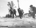 US Marines at Tarawa, Gilbert Islands, 20-23 Nov 1943. Note 2-man .30 cal machine gun team (gunner with the gun on his shoulder and loader two steps ahead with tripod).