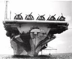 Bow on view of USS Hornet (Essex-class) at anchor in Berth X-14, Majuro Lagoon, Marshall Islands, 29 May 1944. Note F6F Hellcat fighters spotted on the flight deck.