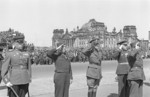 Allied officers during a parade in Berlin, Germany, 6 May 1946; note ruins of Reichstag building in background