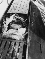 Photograph of a damaged German torpedo lodged in the deck works of the captured U-505 before United States Navy ordinancemen removed it and jettisoned it, 9 Jun 1944