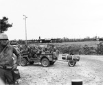 A Jeep full of US 101st Airborne paratroopers at a Normandy check-point, Jun 1944. Note Horsa gliders in the background and a box of full M1 Garand ammunition clips in the immediate foreground behind the MP's leg.