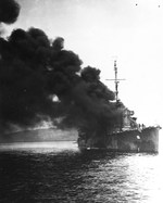 USS Ward on fire and sinking after being struck by a Japanese special attack aircraft in Ormoc Bay, Philippines, 7 Dec 1944, three years to the day after she fired the first US shot of the Pacific War.