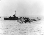 Destroyer USS William D Porter lay mortally wounded by a Japanese special attack aircraft that hit the water close aboard without striking the ship but exploded beneath the ship, off Okinawa, 10 Jun 1945