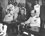 British Rear Admiral Cecil Harcourt reading the terms of surrender to the Japanese representatives, Government House, Hong Kong, 16 Sep 1945. At left is Chinese Major General Pan Hwa Kuei and far left is Adm Bruce Fraser