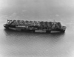 Escort carrier USS Long Island in San Francisco Bay, California, United States, on 10 Jun 1944 with a deck load of F6F Wildcat, SBD Dauntless, and J2F Duck aircraft bound for Pearl Harbor, Hawaii.