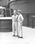 Admiral Raymond Spruance (left) speaking with Captain Carl Holden, commanding officer of USS New Jersey on the New Jersey's foredeck at Majuro, Marshall Islands, 8 Apr 1944. Admiral Nimitz was also on board.
