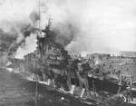 USS Franklin burning and listing after being hit by a Japanese bomb off Japan, 19 Mar 1945. Note firefighting water pouring off the hangar deck into the sea. Photo taken from USS Santa Fe.