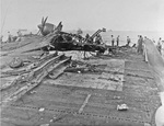 What is left of an SB2C Helldiver on the heavily damaged flight deck of the USS Randolph after a P1Y Ginga special attack bomber crashed into the ship while at anchor in Ulithi Lagoon, Caroline Islands, 11 Mar 1945.