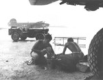 US Navy maintenance crews with Bombing Squadron VB-106 clean engine parts under an airplane wing during a downpour at Momote Airstrip, Los Negros, Admiralty Islands, Mar 1944. Note Jeep and Army SB-24D Liberator.