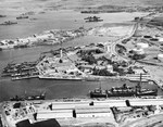 Aerial view of the Pearl Harbor Submarine Piers at Merry Point, 13 Oct 1941. Also pictured is the U-shaped Headquarters Building for the Pacific Fleet and a tank farm at right. Note one tank painted as a building.