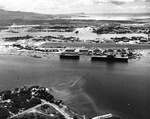 Aerial view of Ford Island from over Pearl City Peninsula looking toward Diamond Head in the distance, 1 Aug 1942. Escort carrier USS Long Island and Yorktown-class carrier USS Hornet are moored to Ford Island.